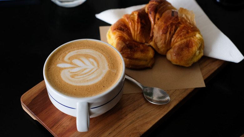 Latte with croissant on table