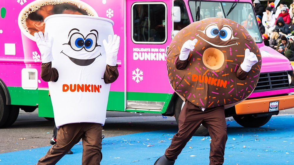 People in Dunkin' doughnut and coffee costumes