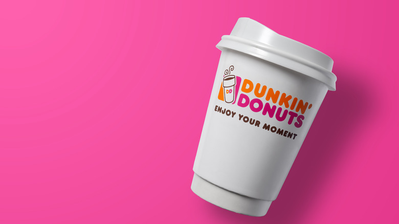 Dunkin' coffee cup against pink background