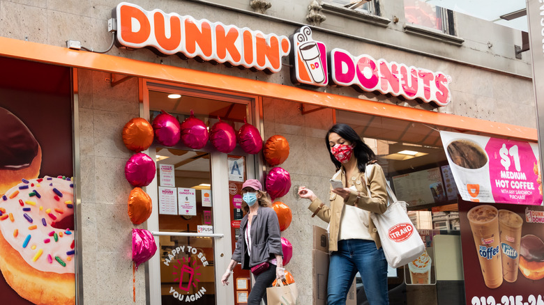 woman in front of a Dunkin' Donuts store