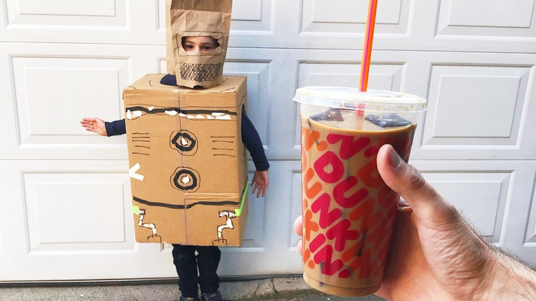 hand holds Dunkin' Donuts with costumed child