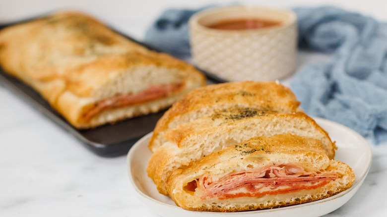 stromboli on a white plate with a container of dipping sauce  and a baking tin of stromboli nearby