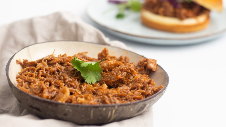 Pulled pork in serving dish with cilantro garnish