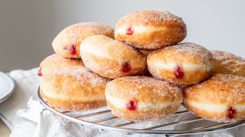 silver wire cooling rack of donuts covered in granulated sugar and filled with seedless raspberry jam