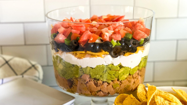 Easy Layered Taco Dip Recipe in bowl with tortillas on side