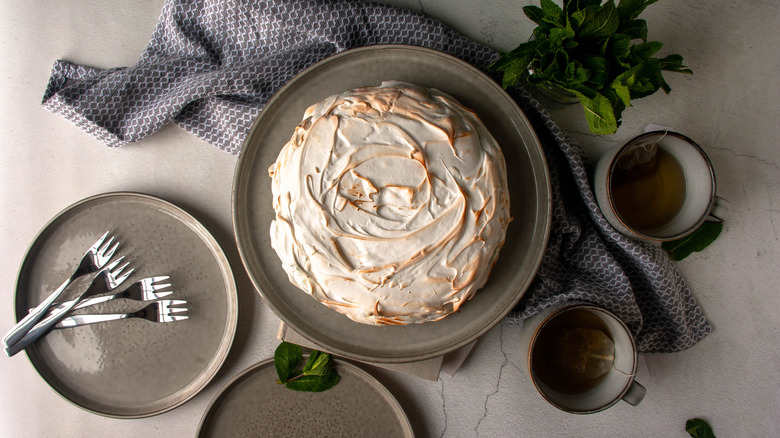 mint baked Alaska on plate from above with mugs of tea and forks