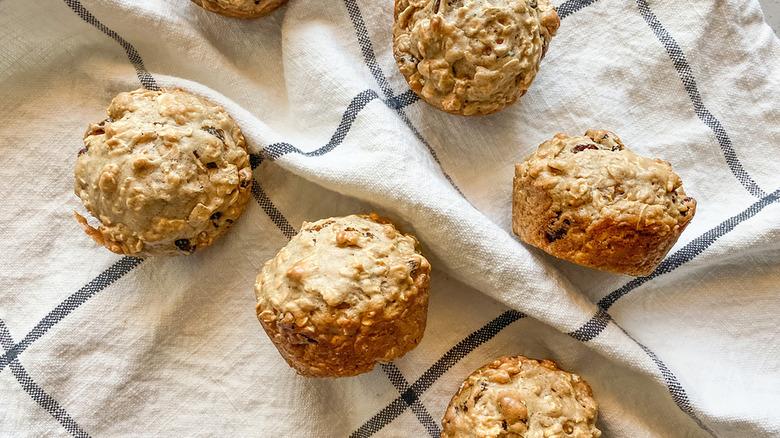 Oatmeal raisin muffins on a tea towel