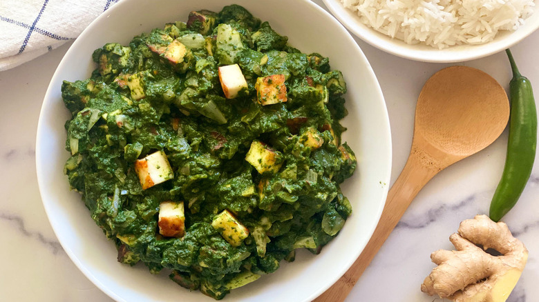 bowl of palak paneer with rice on side