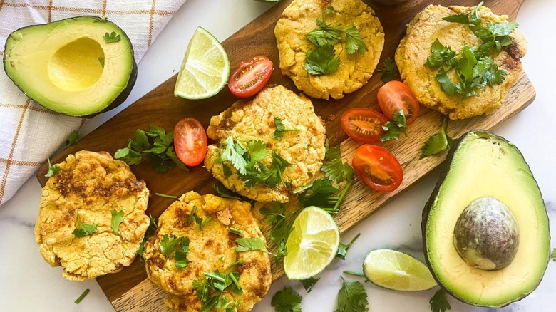 Decorated Pupusas on platter with cherry tomatoes, lime wedges, and avocado halves