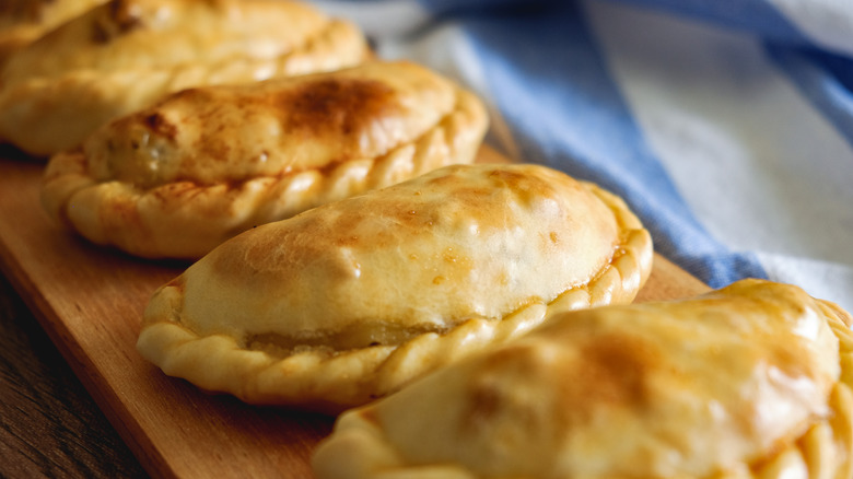 Row of empanadas on a wooden serving dish