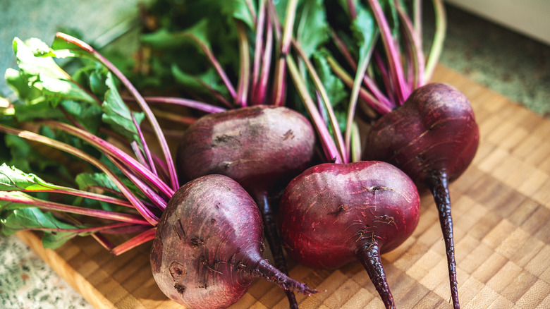 Four whole raw beets on cutting board