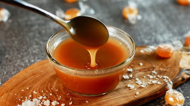 Spoon dipped into bowl of caramel