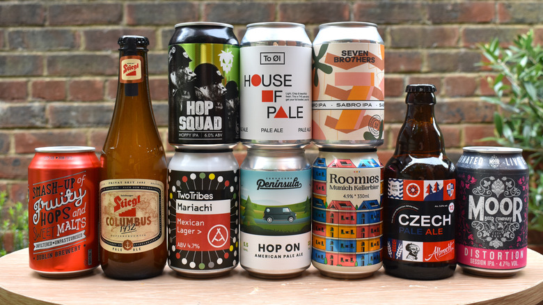 A collection of various pale ales in bottles and cans on a tabletop