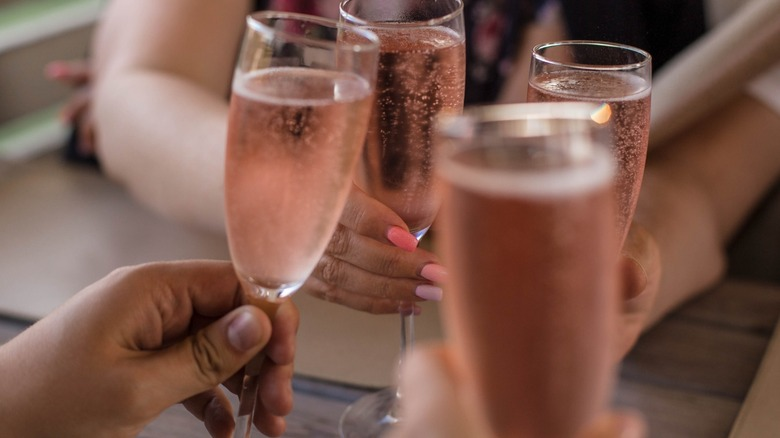 People doing a cheers with glasses of Prosecco rosé