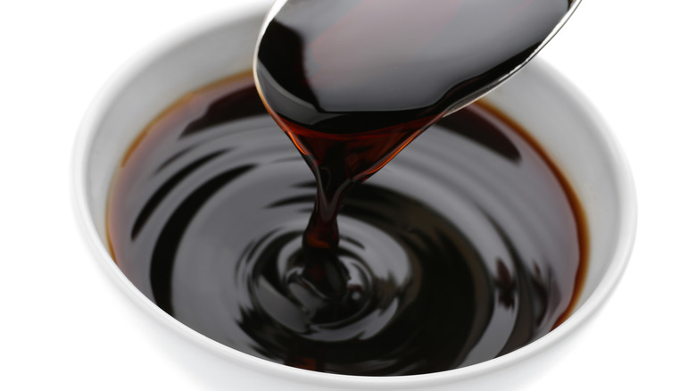 Spooning soy sauce into a white bowl