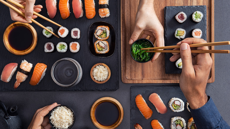 Hands with chopsticks reaching for sushi