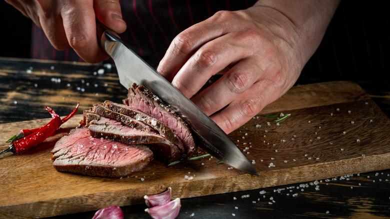 someone cutting a steak