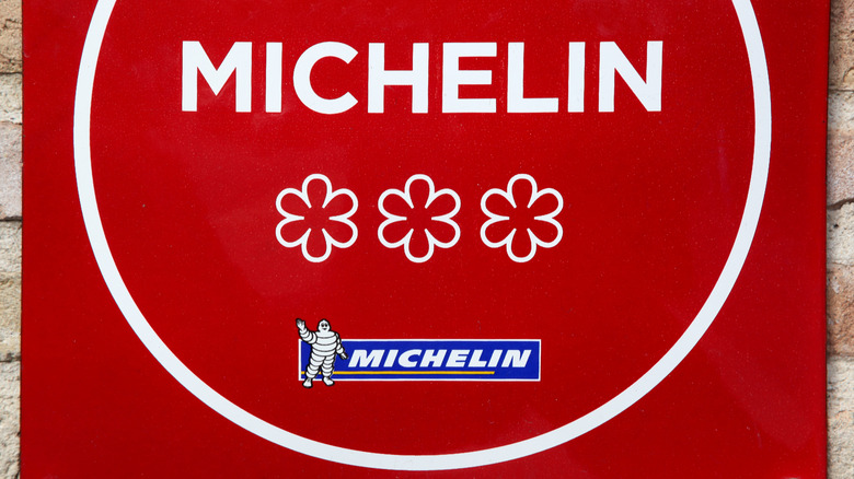 A red Michelin plaque imprinted with three stars