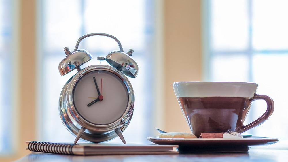 Alarm clock next to coffee mug
