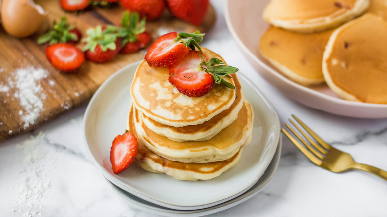 A plate of strawberry pancakes topped with strawberries next to a cutting board with strawberries and a plate with more pancakes