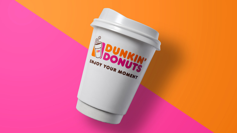 Dunkin' coffee cup on orange and pink background