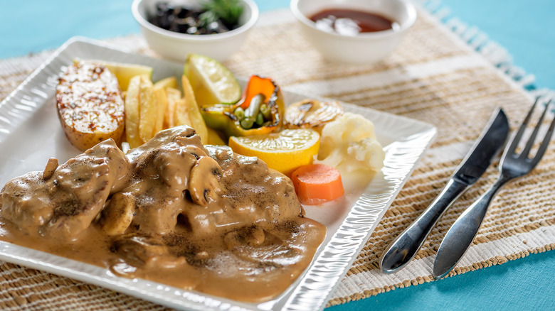 A steak with mushroom sauce on a white plate