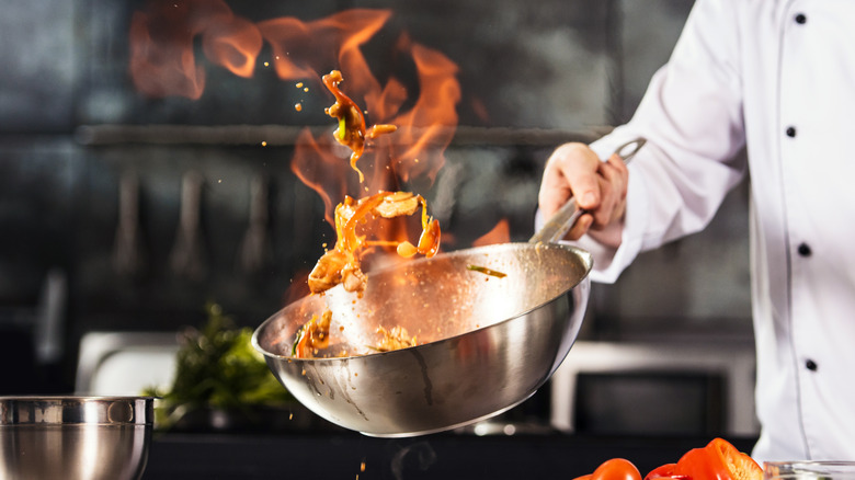 Chef tossing flaming food in wok
