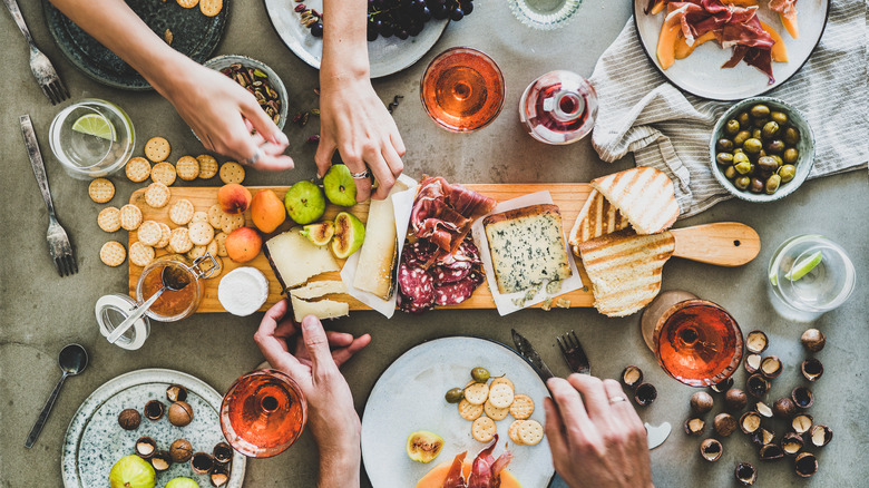 hands over a charcuterie board