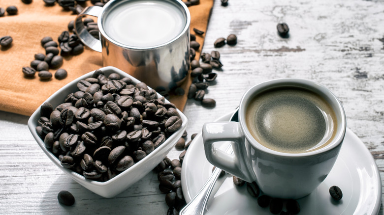 Espresso and fresh coffee beans with steamed milk on a table
