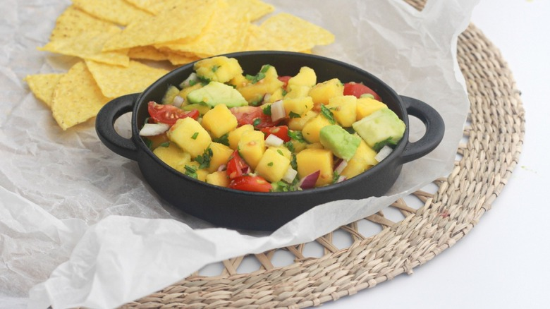 Tortilla chips on a plate with mango salsa and half a lime