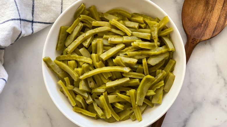 Fresh Nopalitos strips in bowl with wooden spoon