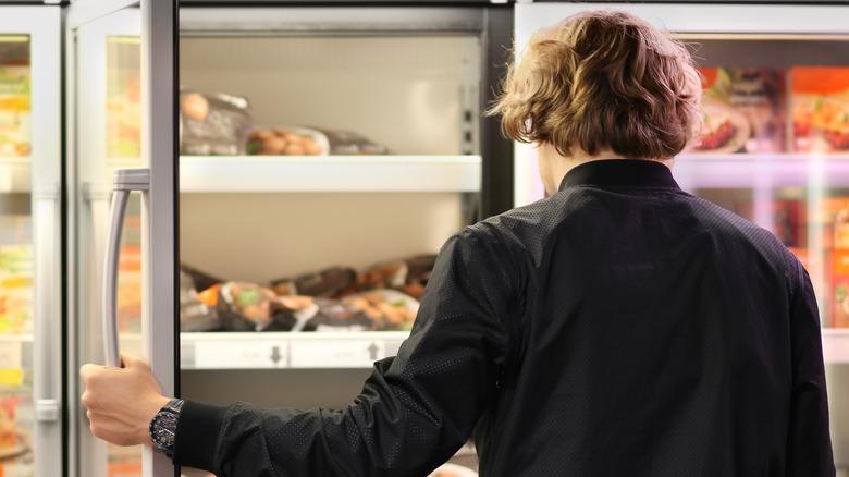 man buying frozen chicken in grocery