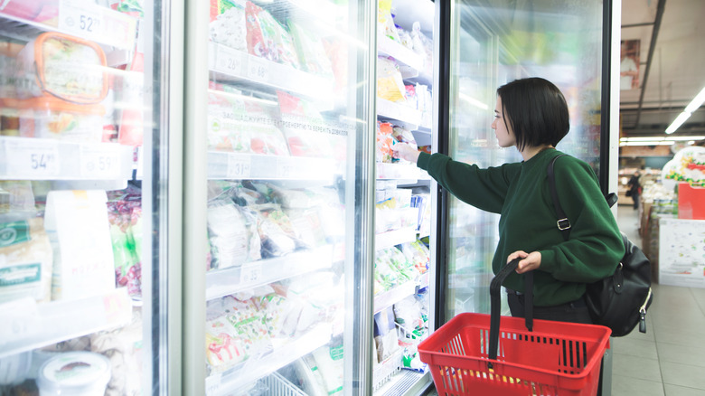 A woman shops for food in the frozen meals aisle