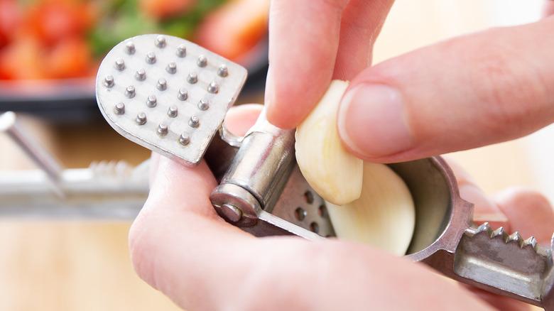 Person putting garlic in garlic press