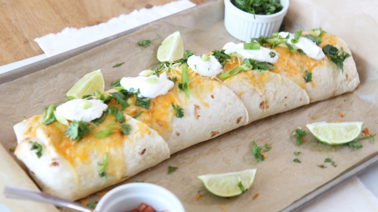 Giant burrito on tray with lime and sour cream