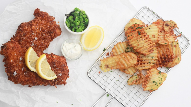 Two pieces of fried cod, mushy peas, tartar sauce, lemon slices, and waffle-cut fries