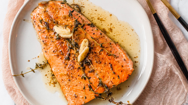 cooked salmon with garlic on plate from above