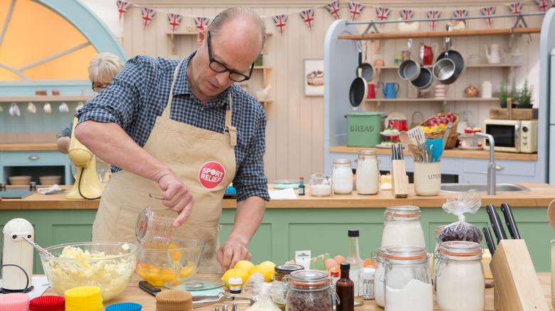 Ade Edmondson pours eggs in kitchen