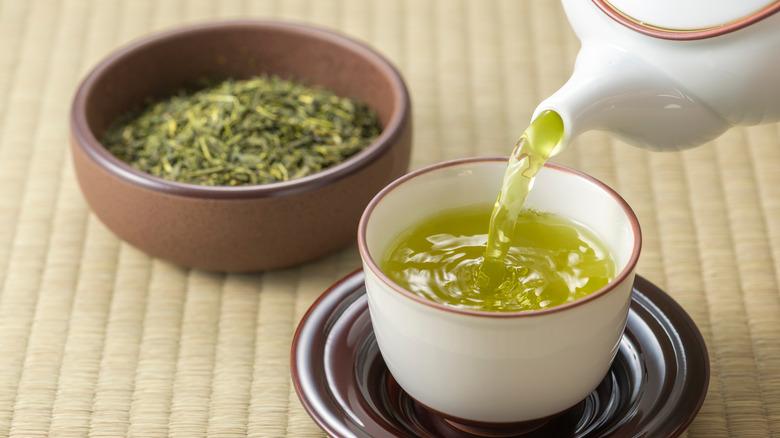 Pouring green tea into a mug