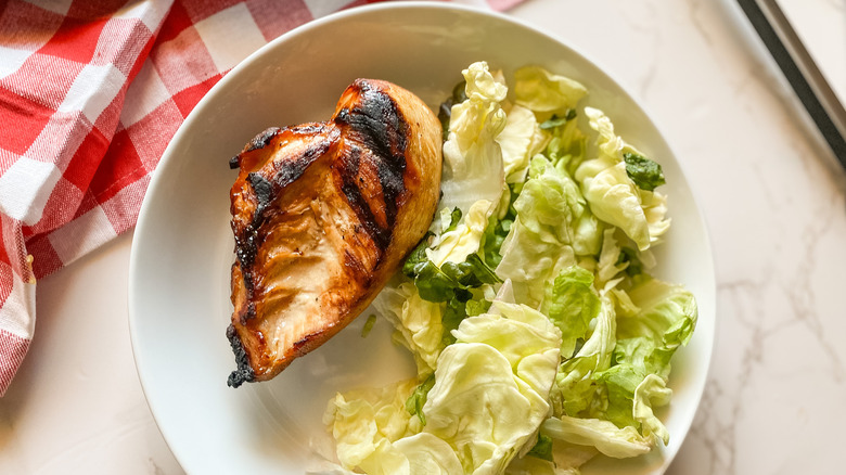 A serving of grilled wedding chicken on a plate with salad