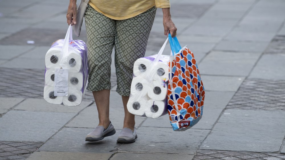 Person shopping with large amounts of toilet paper