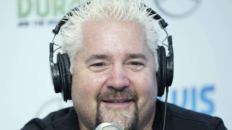 Guy Fieri wearing headphones in front of microphone