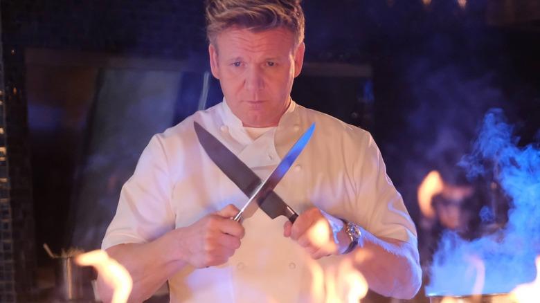 Gordon Ramsay holding knives near flames