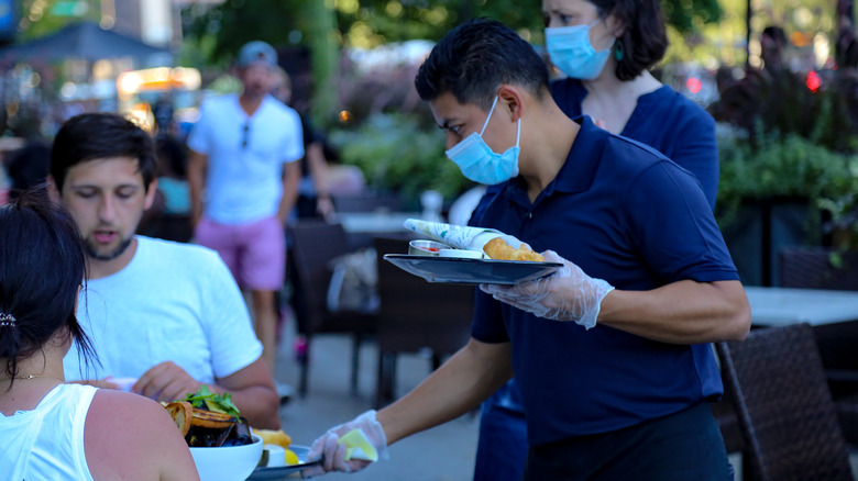 Waiter in face mask serves diners