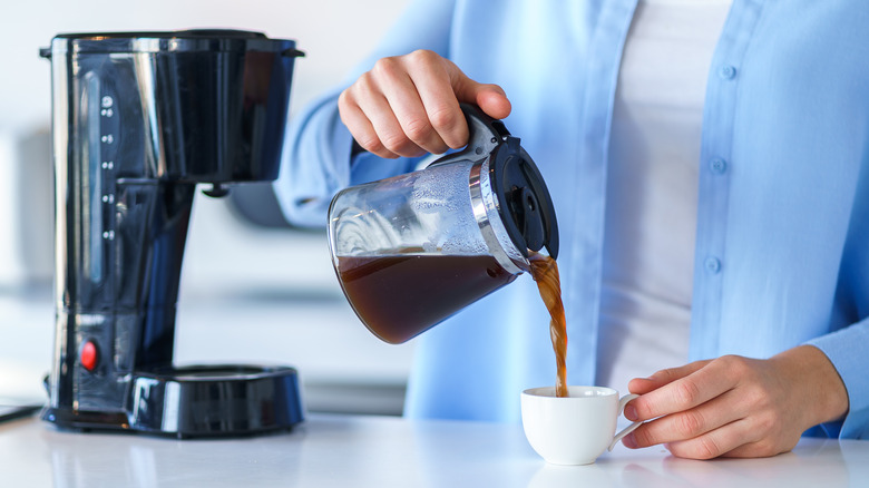 Person pouring cup of coffee