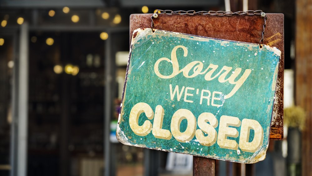 Closed sign in front of shuttered restaurant