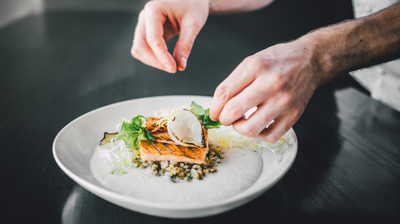 Chef hands perfecting dish