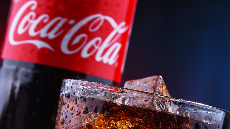 Coca-cola bottle and glass with ice