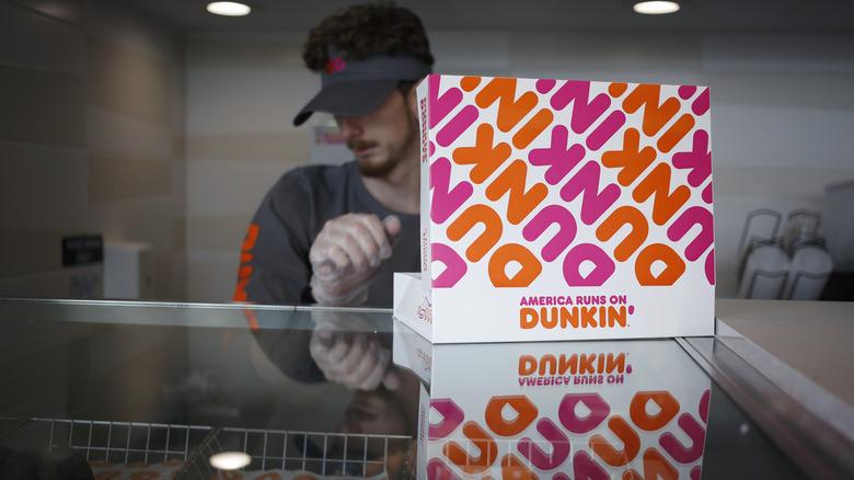 Employee filling open Dunkin' box