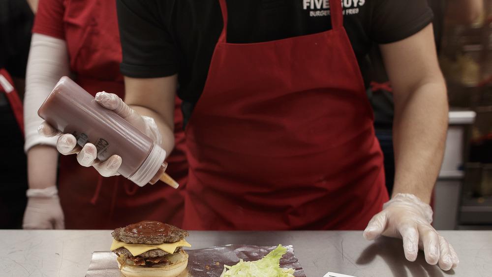 Five Guys employee making a burger